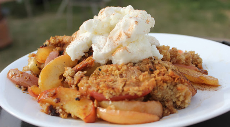 Apple crumble on a plate with cream on top