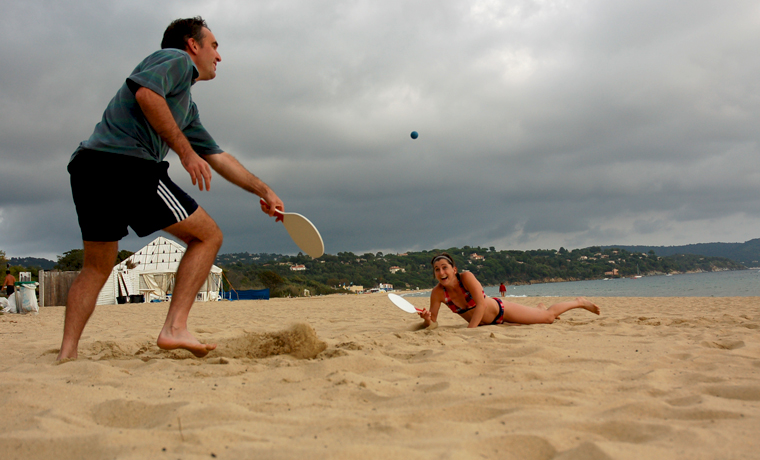 Couple playing bat and ball on the beach