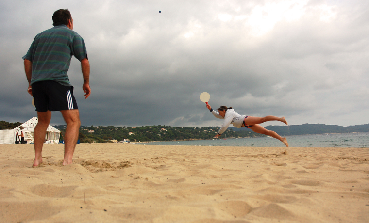 Two people playing one of the best beach games - bat and ball