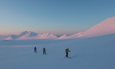 3 Skiers touring across snowy landscape