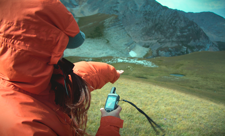 Woman in mountains with gps