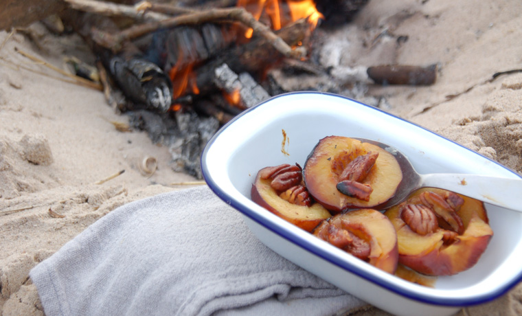 Pecan peaches by a campfire