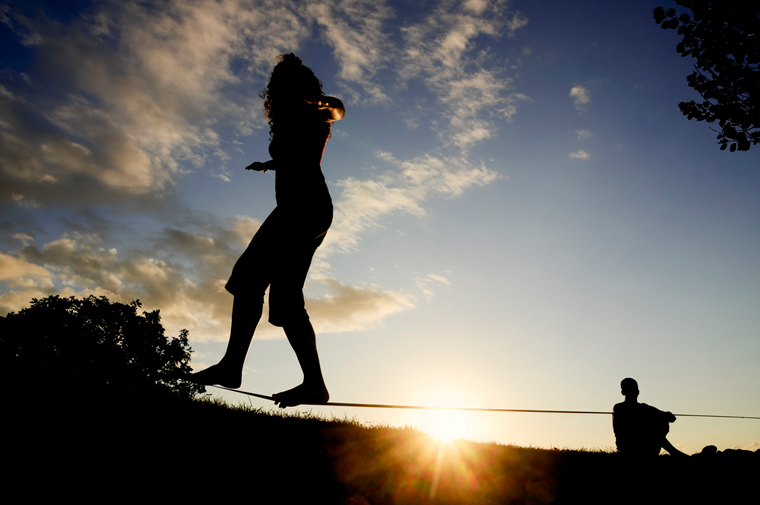 Silhouette of couple slacklining