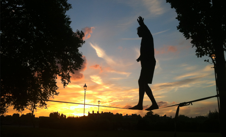 Sunsent silhouette of man on a slackline