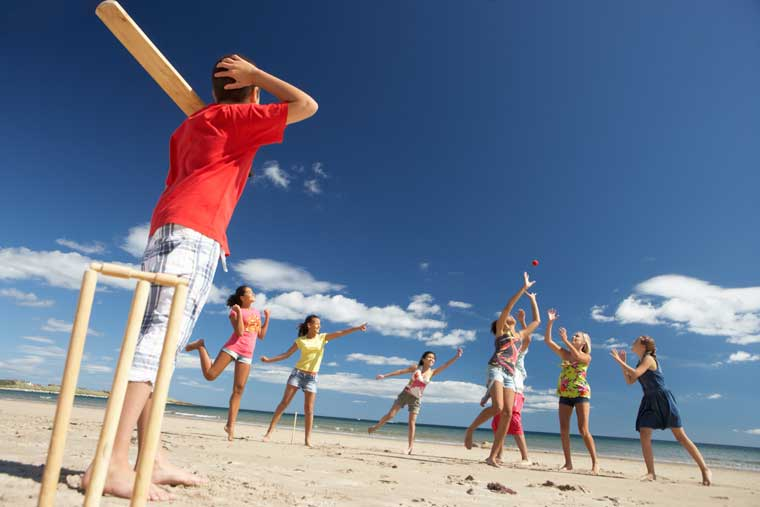Kids playing cricket at the beach