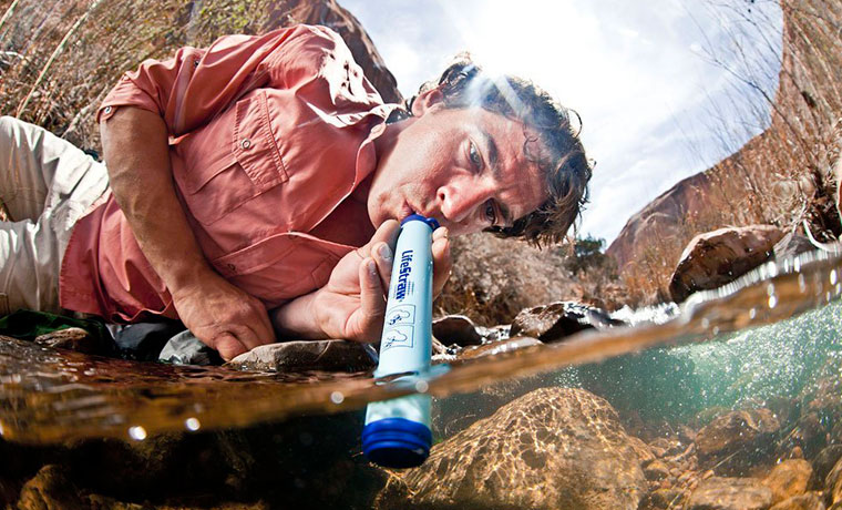 Man drinking water from a stream through a LifeStraw