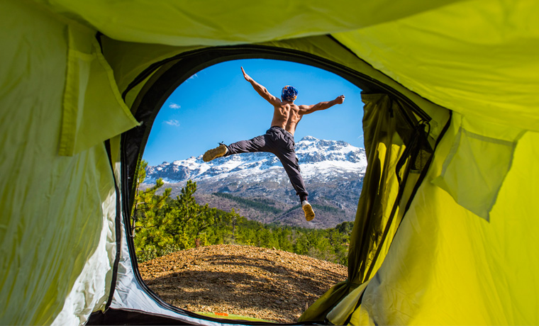 Man jumping out of tent