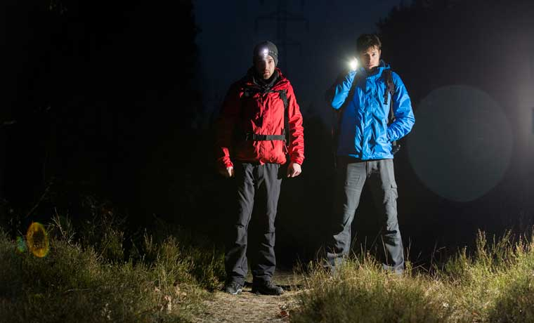 Men with torches hiking at night