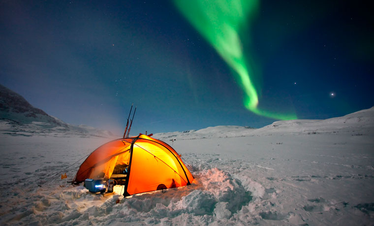 Cold weather tents in the snow with northern lights