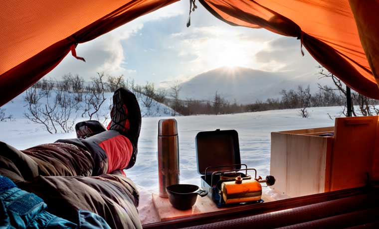 Man sitting in entrance of cold weather tents & Cold Weather Tents: The Best Winter Tents in 2018 - Cool of the Wild