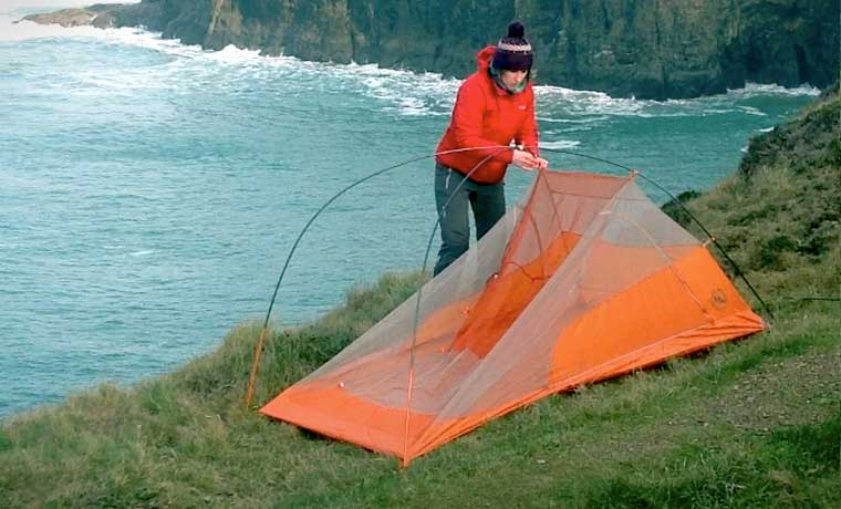 Woman showing how to set up a tent
