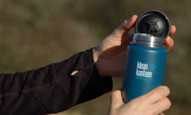 Open insulated flask in hands