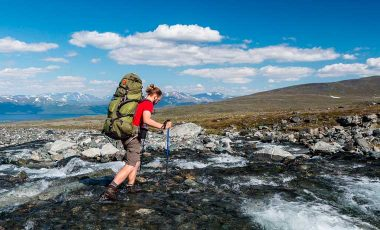 Man crossing river with hiking poles