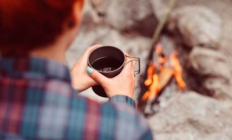 Drinking backpacking coffee by the fire