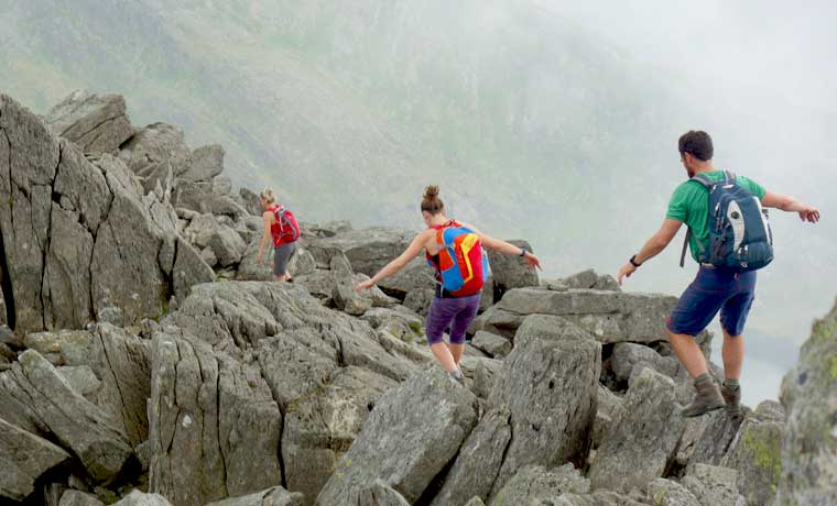 Hikers carrying daypacks on rocks
