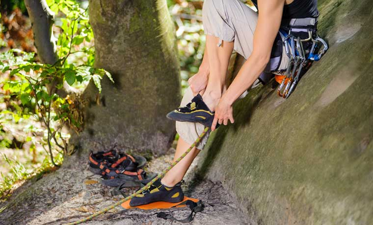 Woman putting on the best climbing shoes