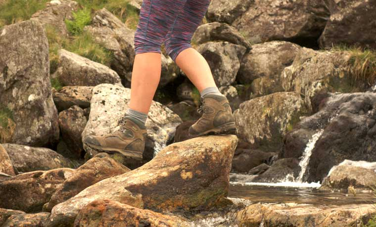 Woman walking over stream in boots