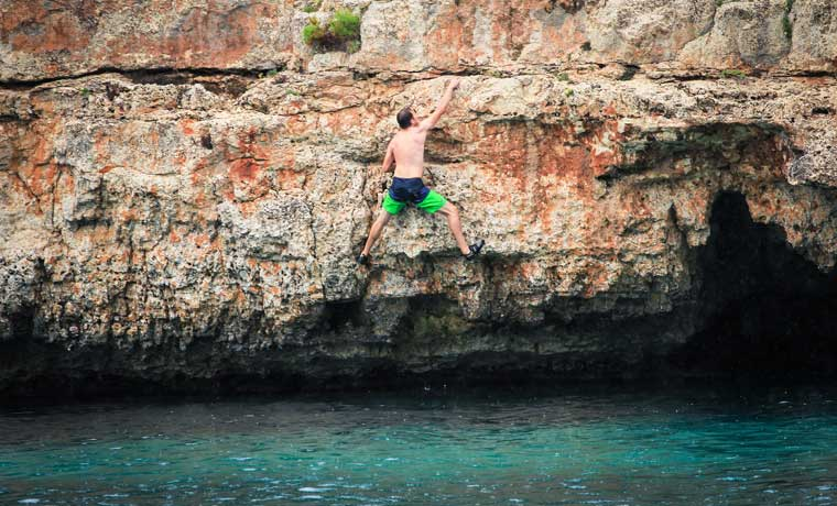 Man climbing over water
