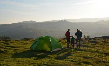 Family standing next ti tent