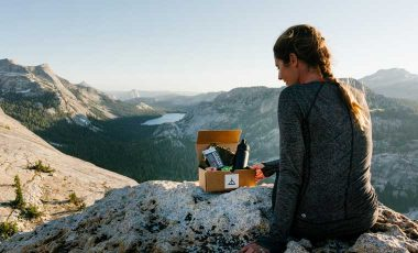 Woman sitting on rocks with adventure box