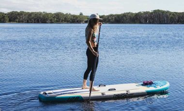 Woman learning how to stand up paddle board