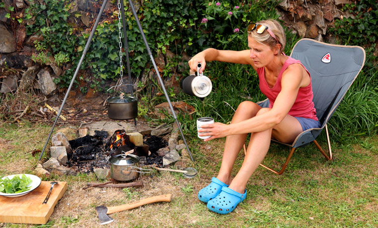Woman pouring coffee next to campfire