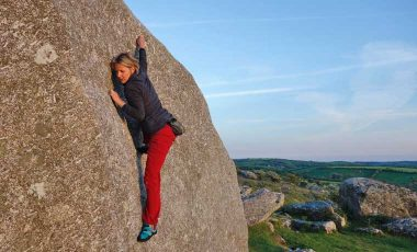 Woman bouldering in red climbing pants