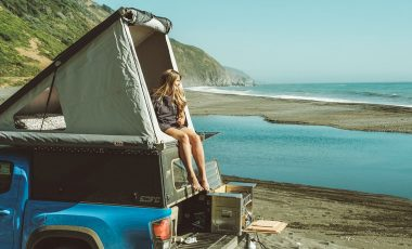 Woman in rooftop tent by the ocean