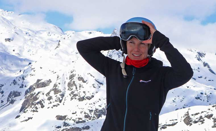 Woman adjusting ski goggles