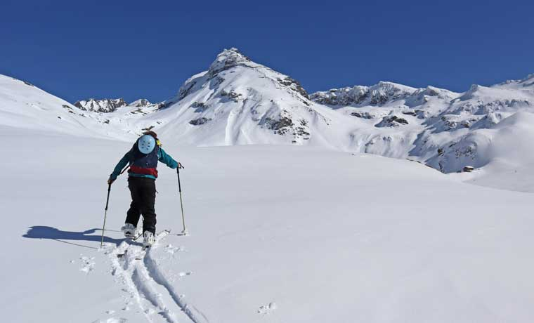 Woman splitboard skinning in the mountains