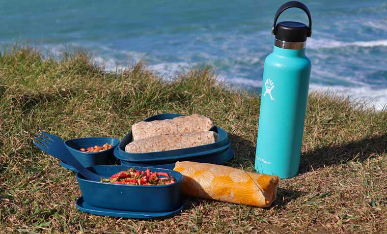 Packed lunch in eco-friendly lunch box by the sea