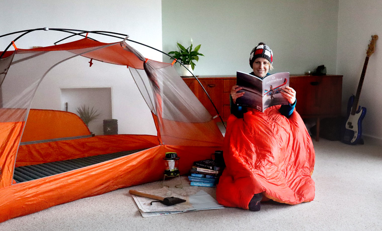 Woman reading next to tent in lounge