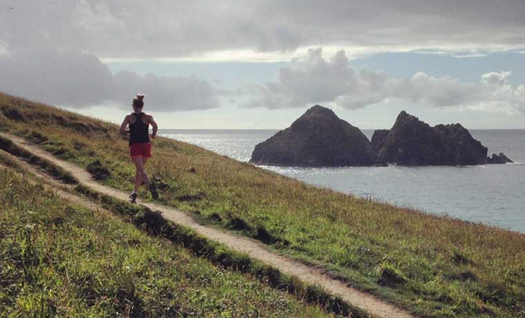 Woman trail running on coast