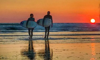Couple walking with surfboards at sunset